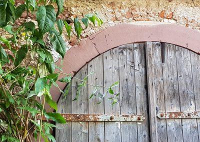 Steinmauer mit Rundbogen und Holztor